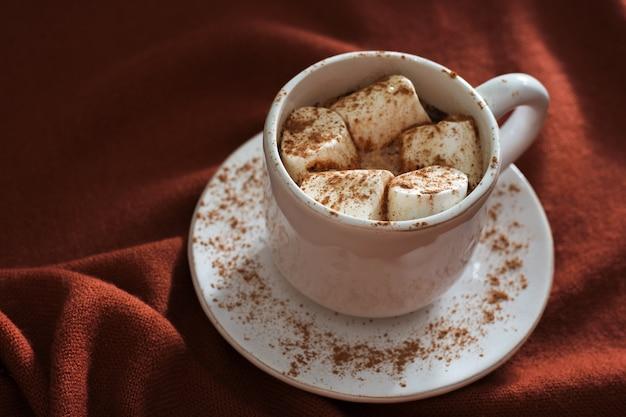 Warme chocola of cacao met marshmallows op gebreide stoffen