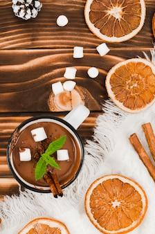 Warme chocola op het bureau met wollen laken, marshmallows en citroenen