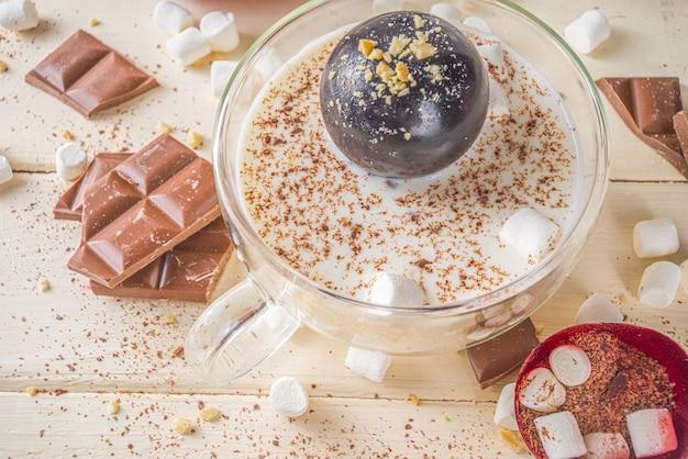 Warme chocoladebom, met marshmallow en chocolaatjes en noten, vrouw hand die chocoladebom in beker met melk laat vallen.