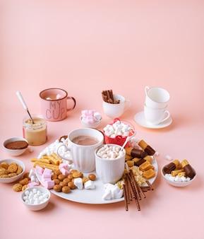 Warme chocoladedrank in mokken, snoep assortiment van marshmallows, chocolaatjes en koekjes op roze tafel