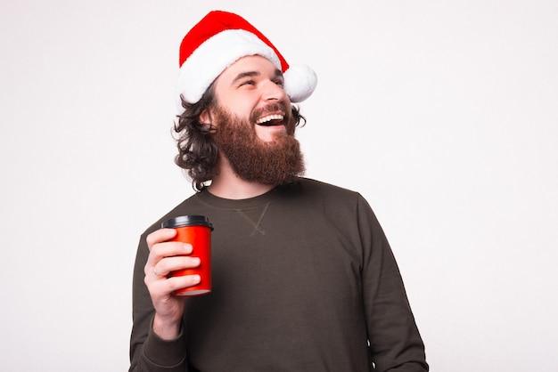 Warme chocolademelk bij koud weer. gelukkig bebaarde man met kerstmuts houdt een beker te gaan.