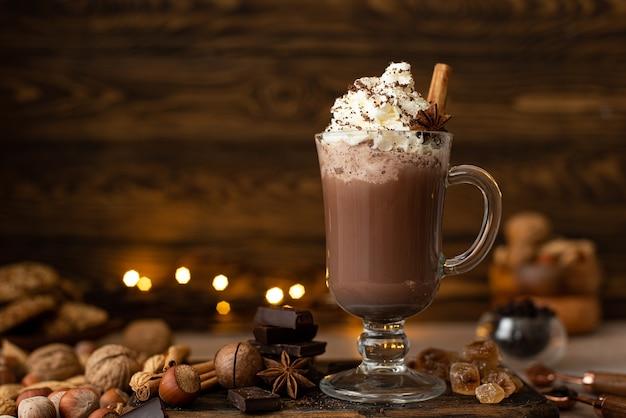 Warme chocolademelk cacao met slagroom en geraspte chocolade in een glazen mok