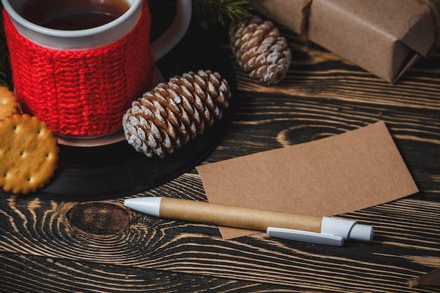 Warme chocolademelk, dennenappel, pen, papier en koekjes