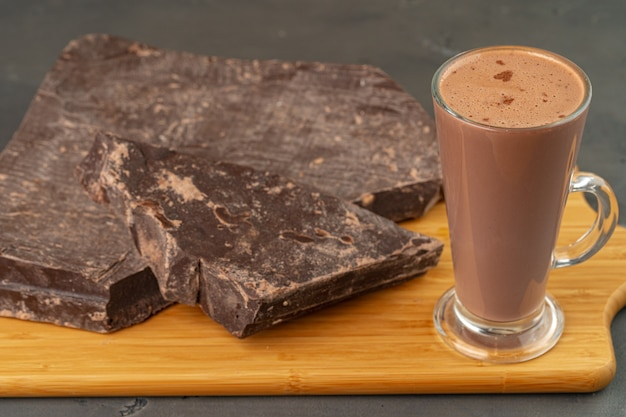 Warme chocolademelk drinken in glazen beker en chocoladereep op grijze achtergrond