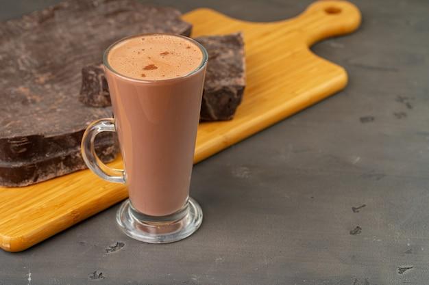 Warme chocolademelk drinken in glazen beker en chocoladereep op grijze tafel close-up