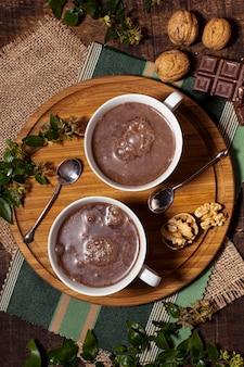 Warme chocolademelk en lepels op een houten bord
