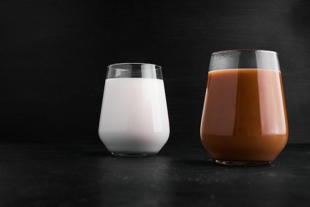 Warme chocolademelk en melk in glazen bekers.