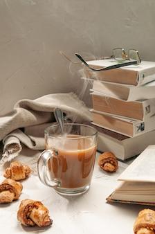 Warme chocolademelk in een doorzichtige glazen mok. in de buurt zijn zelfgemaakte broodjes met noten.