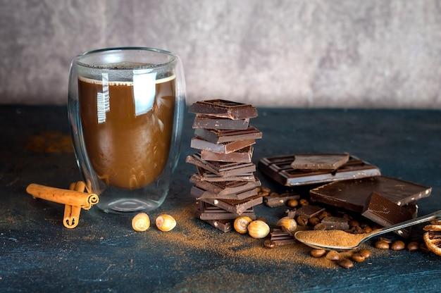 Warme chocolademelk in een glazen mok met kaneel op tafel en een chocoladereep met noten