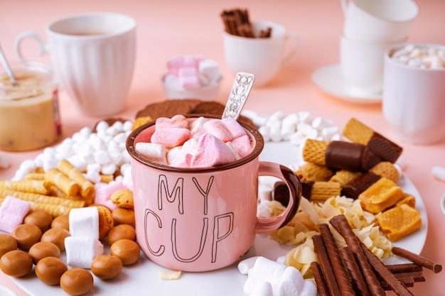 Warme chocolademelk in roze mok, snoep assortiment marshmallows, karamel, chocolaatjes en koekjes op roze tafel