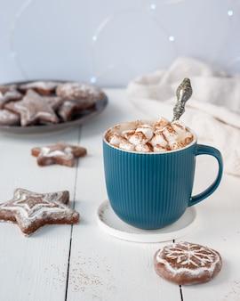 Warme chocolademelk in turquoise beker met marshmallows en peperkoek cookies op een witte tafel