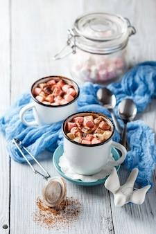 Warme chocolademelk in twee geëmailleerde witte mokken met marshmallow op een lichte houten tafel.