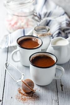 Warme chocolademelk in twee geëmailleerde witte mokken op een lichte houten tafel.