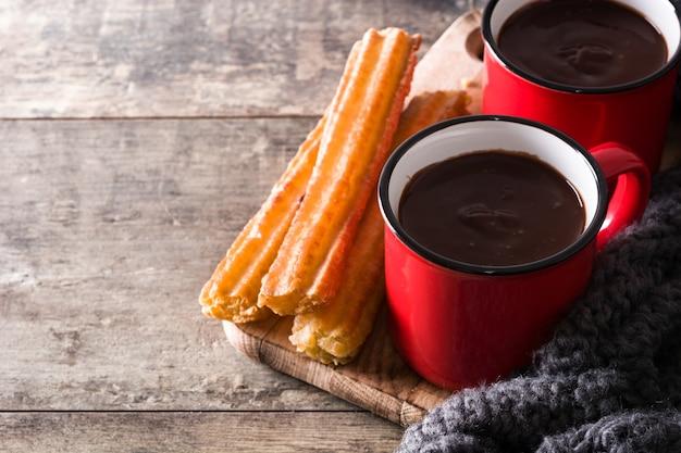 Warme chocolademelk met churros op houten tafel exemplaarruimte