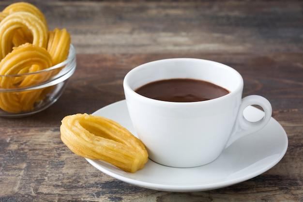 Warme chocolademelk met churros op houten tafel spaans ontbijt