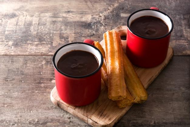 Warme chocolademelk met churros op houten tafel