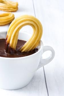 Warme chocolademelk met churros op wit hout. spaans ontbijt