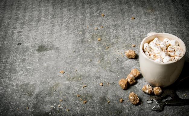 Warme chocolademelk met draadmessen en rietsuiker op betonnen tafel.