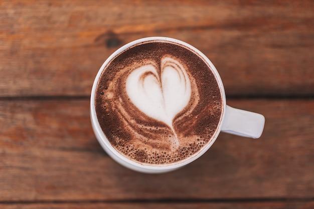 Warme chocolademelk met hartvorm latte art in witte kop