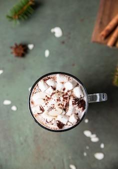 Warme chocolademelk met marshmallow en cacao of chocoladebom wintercompositie met dennentakken en kruiden