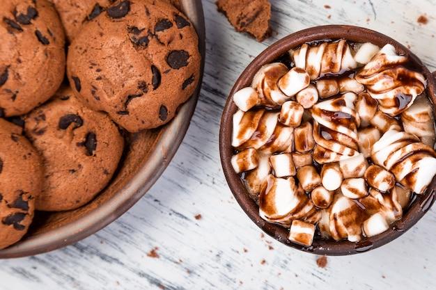 Warme chocolademelk met marshmallow en chocoladekoekjes plat leggen