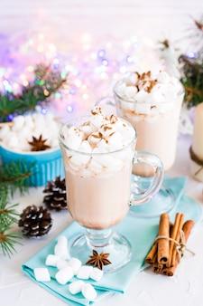 Warme chocolademelk met marshmallow en gemalen kaneel in glazen op tafel in kerstversiering