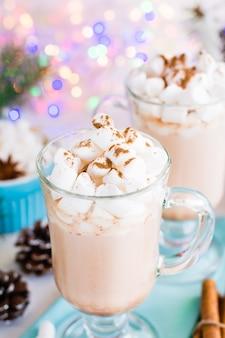 Warme chocolademelk met marshmallow en gemalen kaneel in glazen op tafel