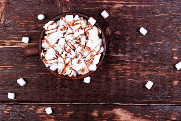 Warme chocolademelk met marshmallow in bruine kop op houten achtergrond