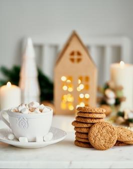 Warme chocolademelk met marshmallow in witte mok omringd door winterkerstversiering