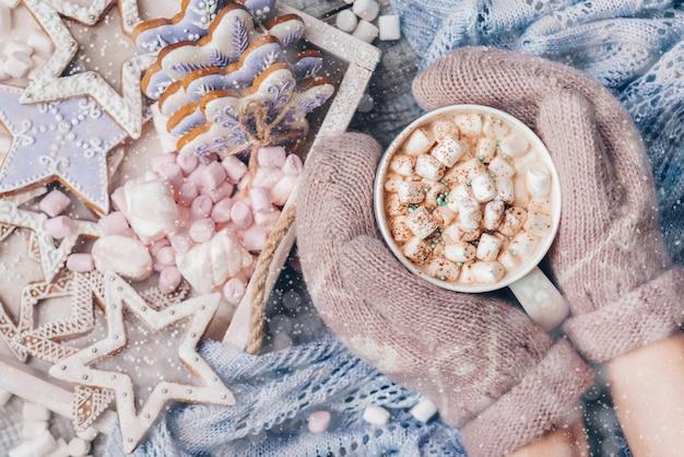 Warme chocolademelk met marshmallow-snoepjes en peperkoekkoekjes vrouwelijke handen in wanten met een warme cococa cup