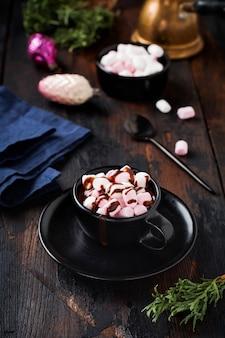 Warme chocolademelk met marshmallow snoepjes in zwarte keramische cup op oude donkere vintage houten oppervlak