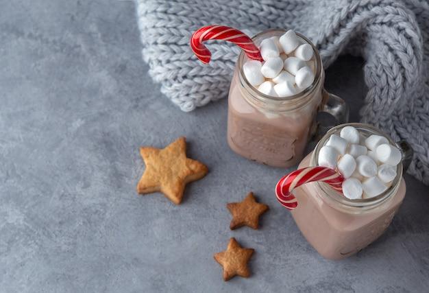 Warme chocolademelk met marshmallows en een suikerriet in glazen mokken op een grijze achtergrond met een gebreide sjaal.