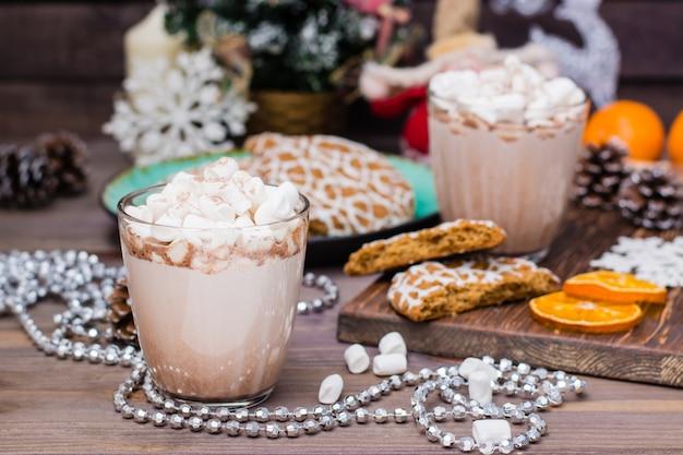 Warme chocolademelk met marshmallows en kaneel in glazen op tafel in kerstversiering