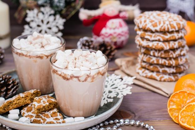 Warme chocolademelk met marshmallows en kaneel in glazen op tafel met kerstversiering