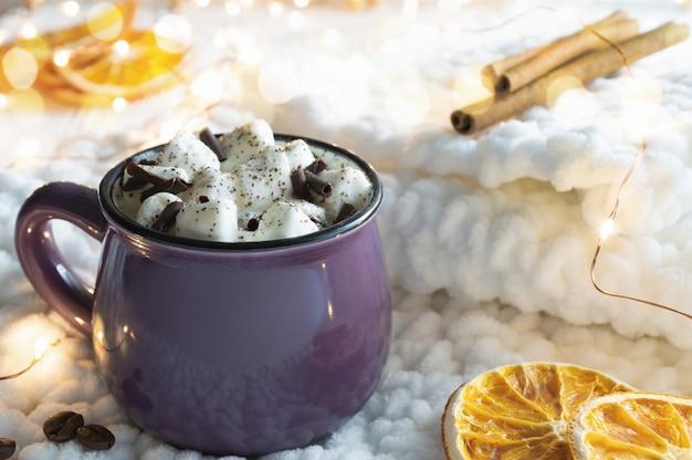 Warme chocolademelk met marshmallows en kerstverlichting op gebreide stof.