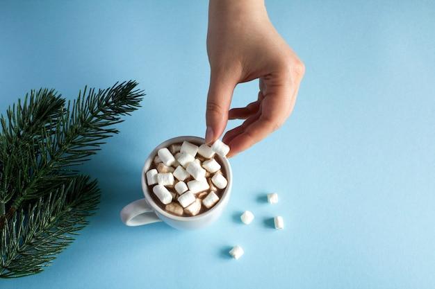 Warme chocolademelk met marshmallows en vrouwenhand op een blauw oppervlak