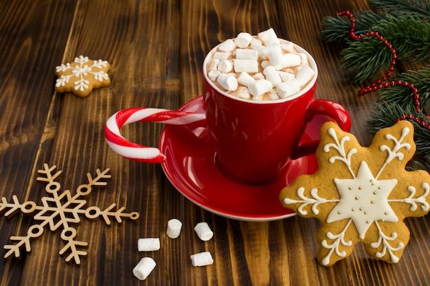 Warme chocolademelk met marshmallows in de rode kop en kerstkoekjes