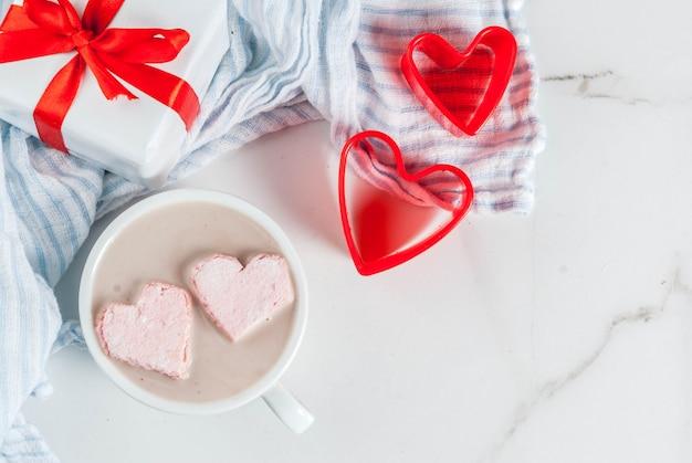Warme chocolademelk met marshmallows in de vorm van harten, valentijnsdagviering, met rode koekjessnijders en de geschenkdoos van valentijnsdag