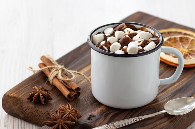 Warme chocolademelk met marshmallows in een vintage mok van wit metaal