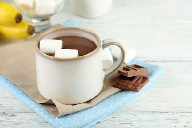 Warme chocolademelk met marshmallows in mok, op houten achtergrond