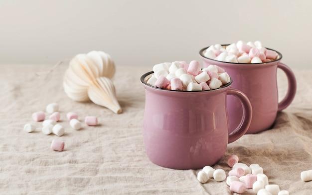 Warme chocolademelk met marshmallows in mokken op een linnen tafelkleed met kerst speelgoed concept van winter h...