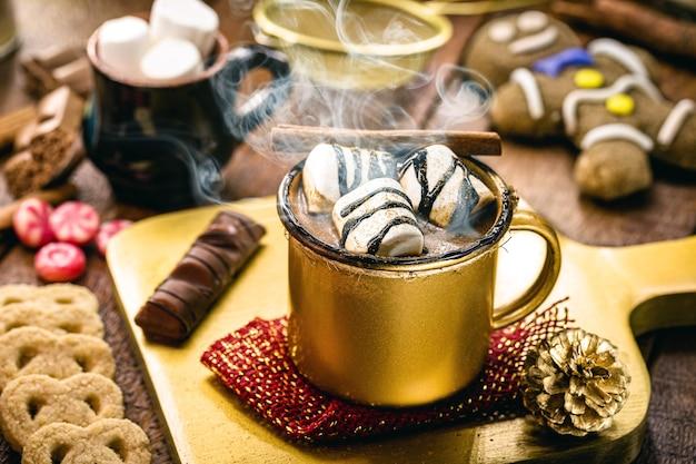 Warme chocolademelk met marshmallows, stoom of rook, zelfgemaakte kerstdrank, met peperkoekmannetje op de achtergrondv