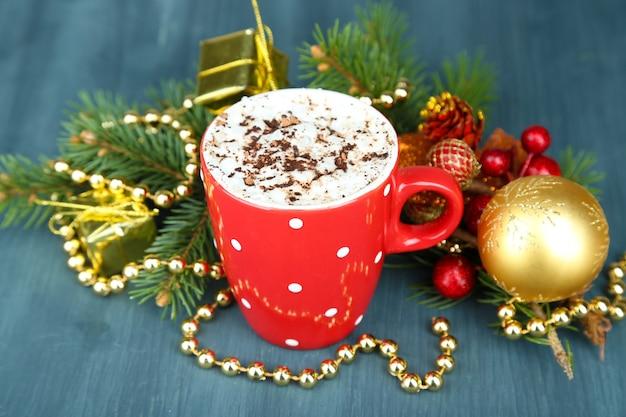 Warme chocolademelk met room in kleur mok, op tafel, op kerstversiering achtergrond