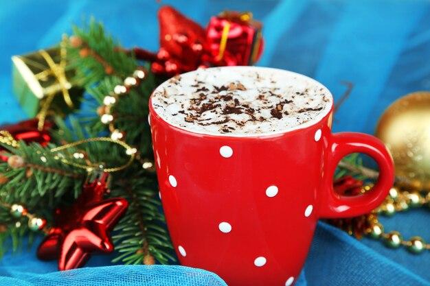 Warme chocolademelk met slagroom in kleur mok, op tafel, op kerstversiering