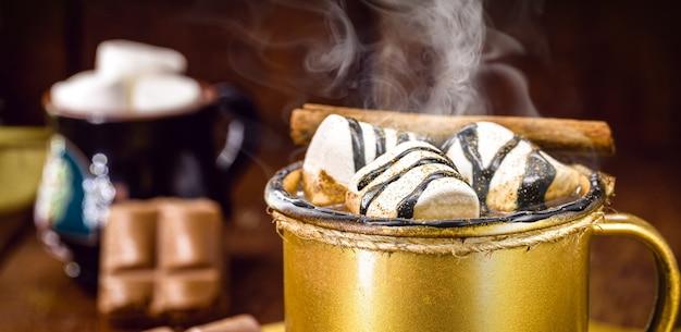 Warme chocolademelk met stoom of rook in een gouden beker met marshmallows en kaneel