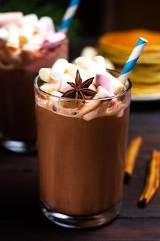 Warme chocolademelk of cacao met gekleurde marshmallows in een glazen glas