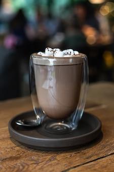 Warme chocolademelk of cacaodrank met marshmallow in glazen beker op houten tafel in café