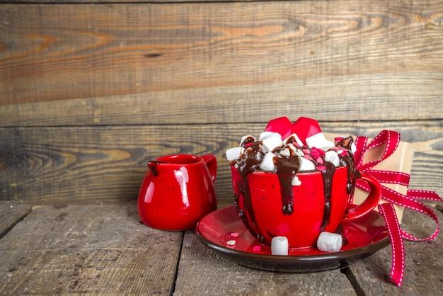 Warme chocolademelk of koffie latte cup voor valentijnsdag ochtend. crazy shake-stijl warme chocolademelk of latte met veel marshmallow en harten suikerstroop, met geschenkverpakkingen en rozenbloemen