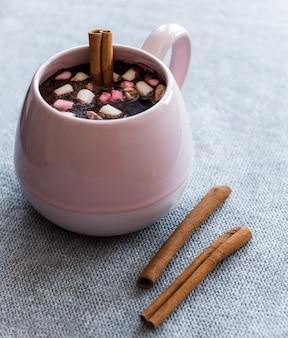 Warme chocolademelk roze keramische mok marshmallows en kaneelstokjes grijze gebreide achtergrond
