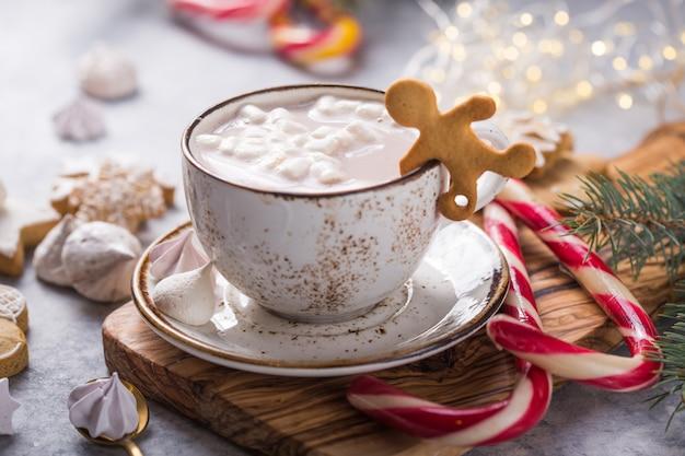 Warme chocolademelkdranken met marshmallows in kerstmokken op grijze ondergrond. traditionele warme drank, feestelijke cocktail op kerstmis of nieuwjaar